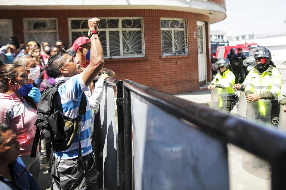 """Angehörige von Häftlingen versammeln sich vor dem Gefängnis """"La Modelo"""". Mindestens 23 Häftlinge sind ums Leben gekommen und 80 weitere wurden dort am Sonntag verletzt."""