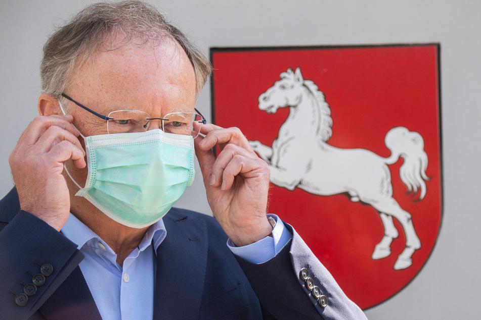 Stephan Weil (SPD), Ministerpräsident Niedersachsen, steht vor der Staatskanzlei und zieht einen Mundschutz an.