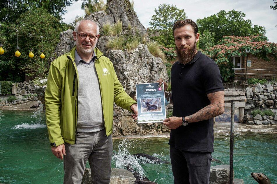 Zoo-Direktor Theo B. Pagel übergibt Marco Höger die Patenschaftsurkunde.
