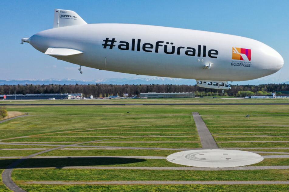 Der Zeppelin NT (Neue Technik) fliegt vor dem Zeppelinhangar über das Flughafengelände. Die Polizei hatte am Nachmittag vom Zeppelin aus kontrolliert, wie sich die Bevölkerung an das Kontaktverbot hält.