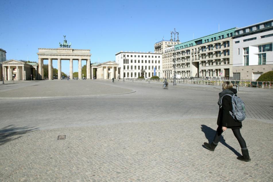 Eine junge Frau geht über den fast menschenleeren Pariser Platz vor dem Brandenburger Tor.