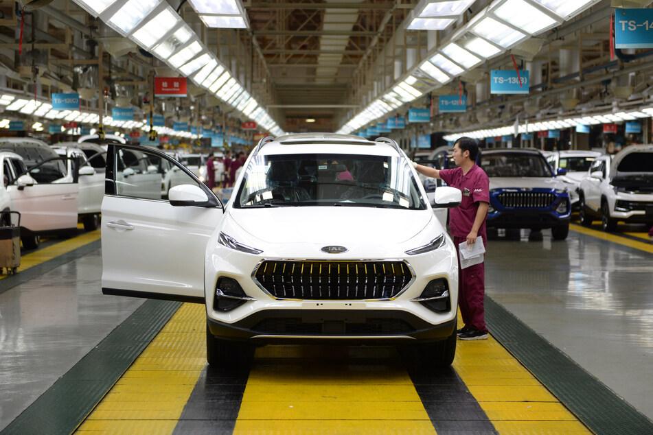 Ein Arbeiter begutachtet ein neu zusammengebautes Auto in einer Fabrik des Automobilherstellers Anhui Jianghuai Automobile (JAC) in der Provinz Anhui.