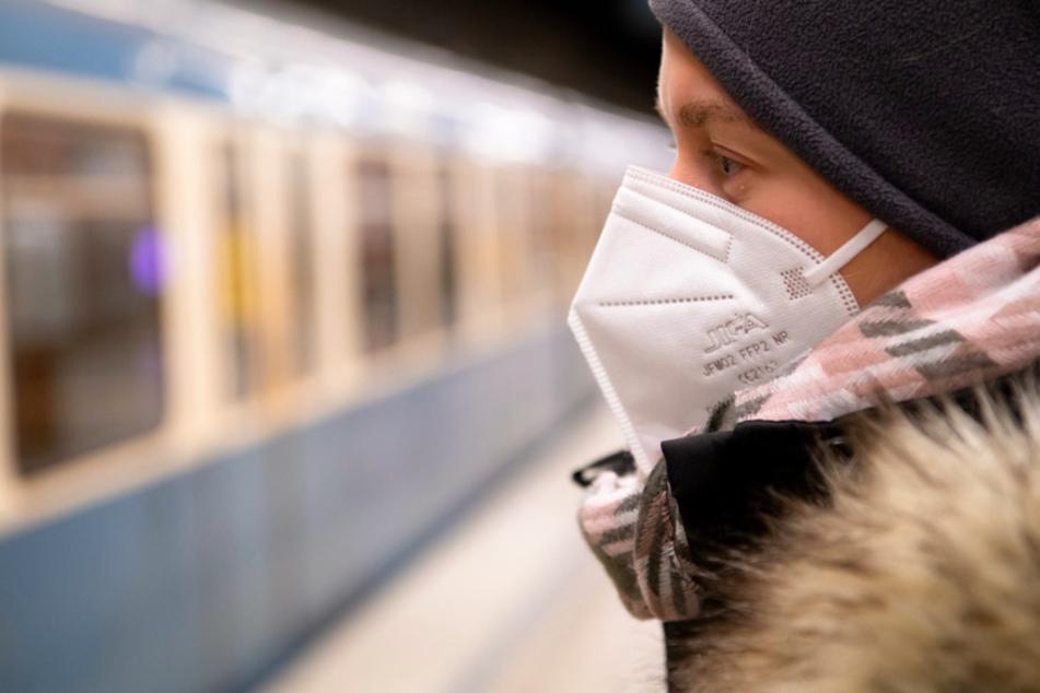 Ein Frau mit FFP2-Maske wartet in einer U-Bahnstation auf die Bahn.