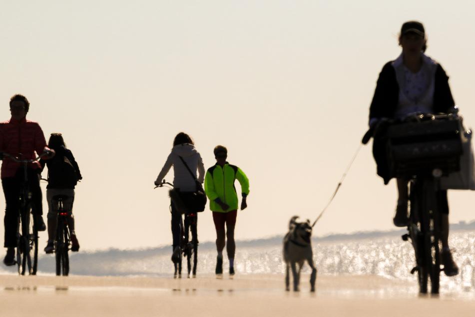 Ein Frau in einer grünen Jacke betreibt bei schönem Wetter an der Strandpromenade die Sportart Walking, während Radfahrer links und rechts an ihr vorbeifahren.