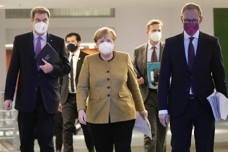Bundeskanzlerin Angela Merkel (CDU), kommt neben Markus Söder (CSU, l), Ministerpräsident von Bayern und CSU-Vorsitzender, sowie Michael Müller (SPD, r), Regierender Bürgermeister von Berlin, zu der Pressekonferenz nach den Beratungen von Bund und Ländern über weitere Corona-Maßnahmen.