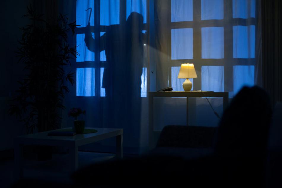 Der Schatten eines Einbrechers an der Balkontür. (Symbolbild)