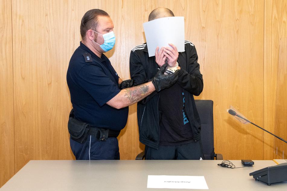 Ulm, 25. August: Ein Justizwachmeister führt den Angeklagten. Dieser versteckt sein Gesicht.