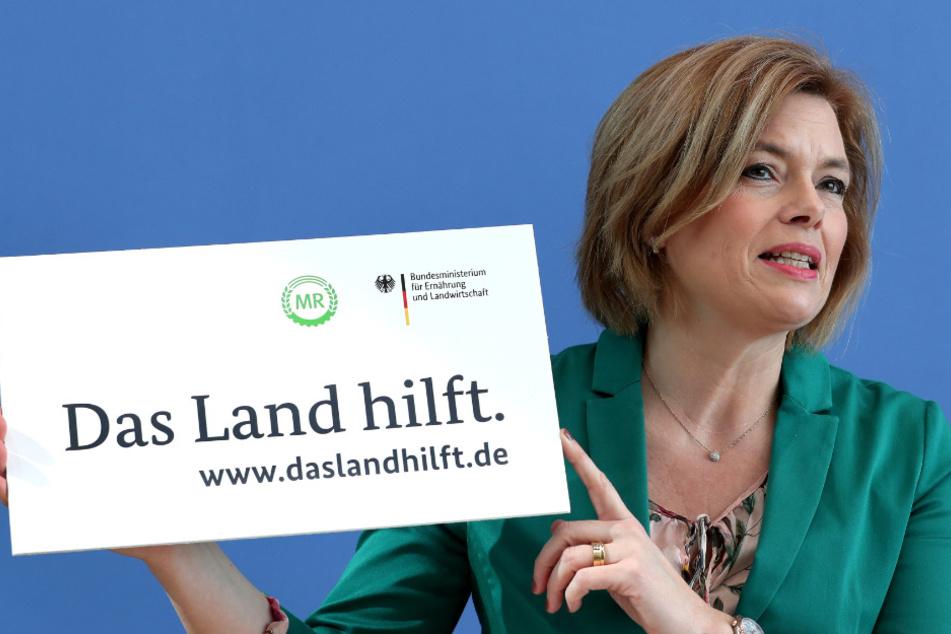 """Bundeslandwirtschaftsministerin Julia Klöckner präsentiert ein Plakat mit der Aufschrift """"Das Land hlift""""."""