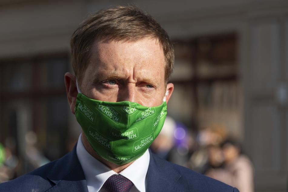 Sachsens Ministerpräsident Michael Kretschmer (CDU) trägt einen Mundschutz.