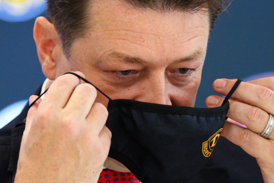 Maske auf! Holger Scholze zieht sich einen Mund-Nasen-Schutz über - natürlich im Dynamo-Design.