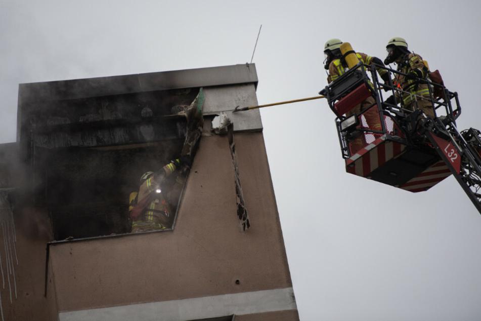 Feuerwehrleute lösen die Verkleidung am Dach eines Hauses. Die Feuerwehr musste am Dienstagvormittag einen Wohnungsbrand in Berlin-Kreuzberg löschen.