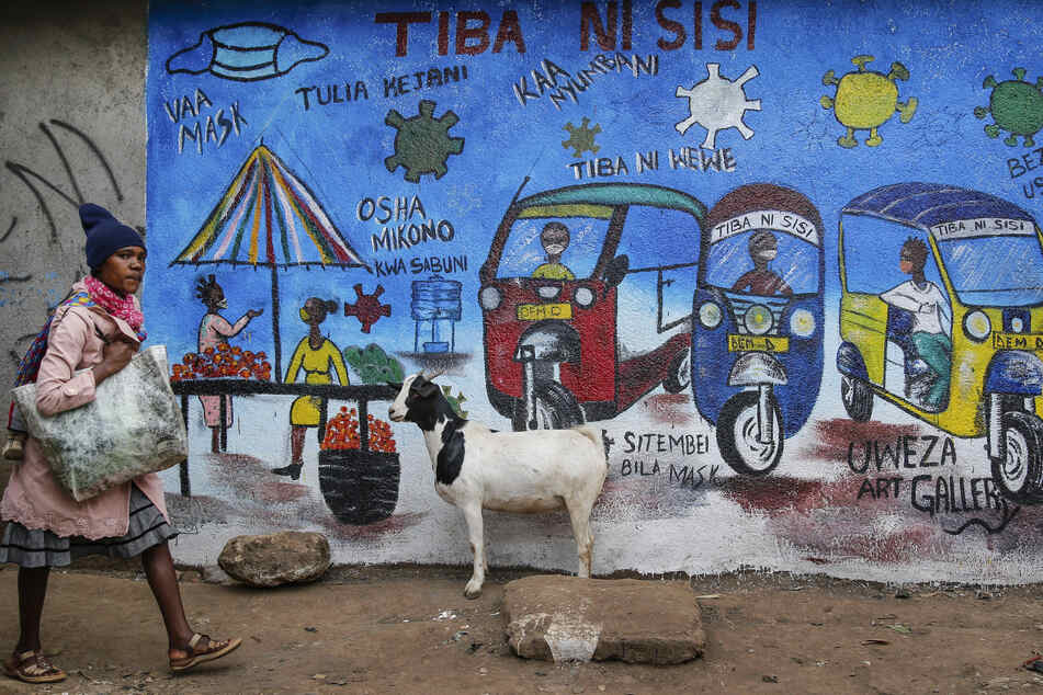 Kenia, Nairobi: Ein Frau geht an einem Wandgemälde vorbei, das über die Gefahren des Coronavirus informiert.