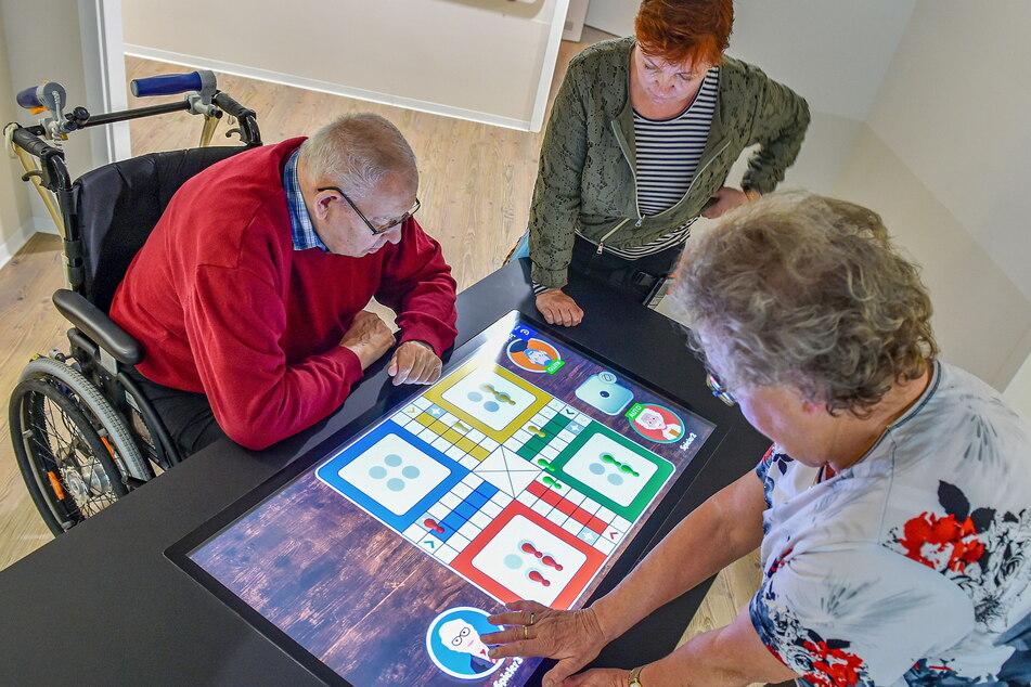 """Hartmut Erhardt (81) und Annemarie Schulze (78) spielen mit Kerstin Leuteritz (53) vom ASB eine Runde """"Mensch ärgere Dich nicht""""."""