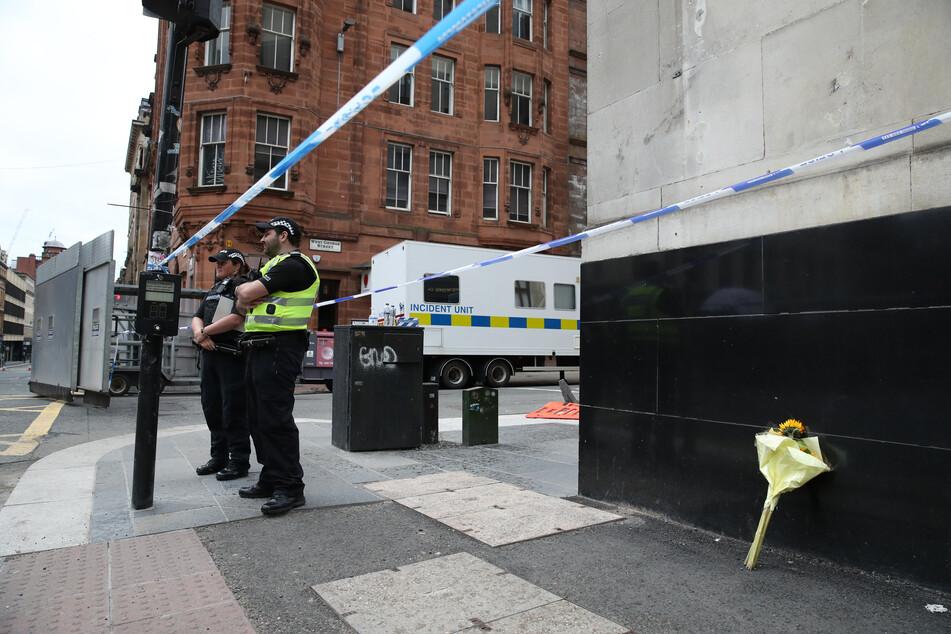 Großbritannien, Glasgow: Polizeibeamte stehen an dem abgesperrten Tatort in der West George Street, an dem ein Blumenstrauß an eine Hauswand gestellt wurde.