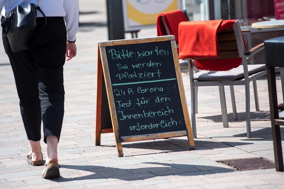 """Schleswig-Holstein, Insel Sylt: Ein Schild mit der Aufschrift """"Bitte warten, Sie werden platziert. 24h Corona Test für den Innenbereich erforderlich"""" steht vor einem Restaurant."""