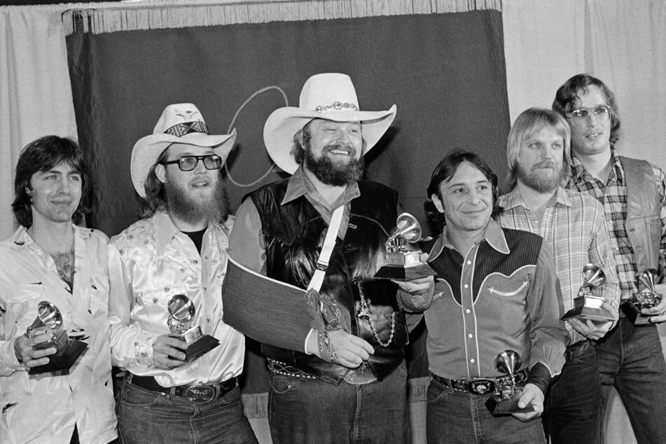 """27. Februar 1980, Los Angeles: Charles Daniels (Mi.), Country-Sänger aus den USA, steht zusammen mit den Mitgliedern der """"Charlie Daniels Band"""" und ihren Grammy Awards für die beste Countrydarbietung einer Gruppe für den Song """"The Devil Went Down to Georgia"""" auf der Bühne."""