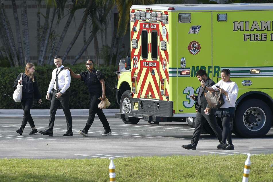 Aventura Mall employees are escorted away by police.