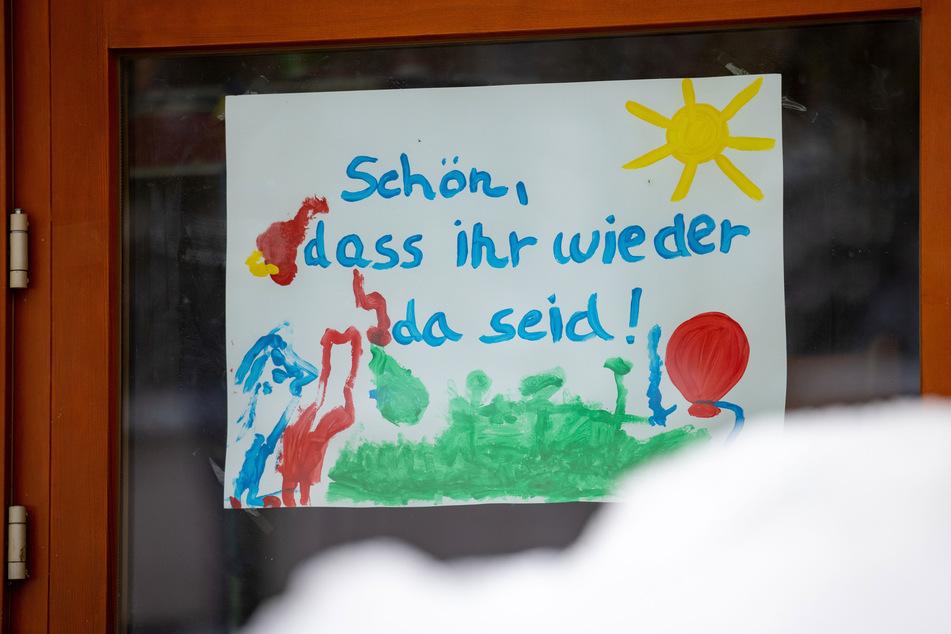 Ein Bild im Eingang eines Kindergartens heißt die Kinder willkommen.