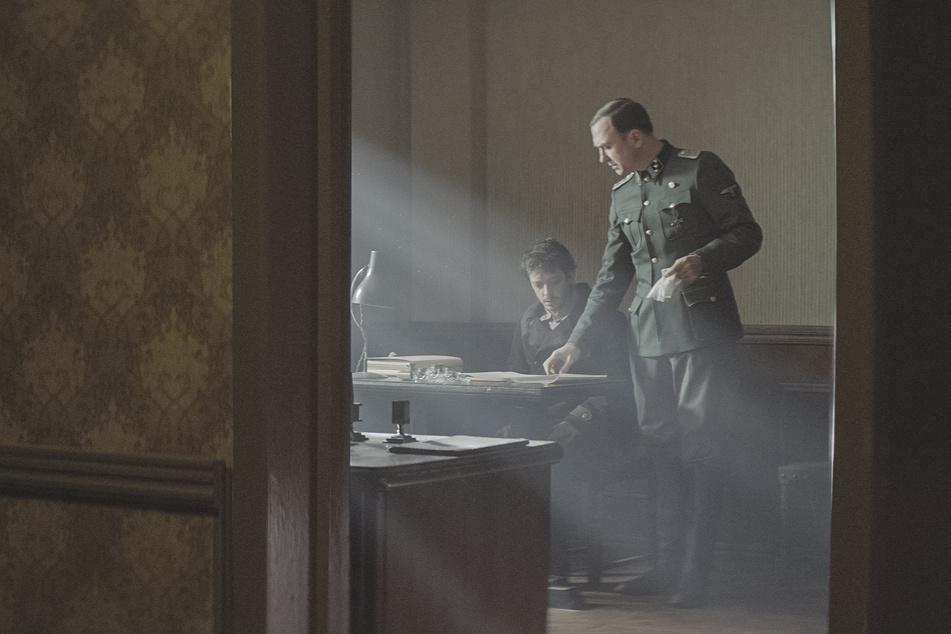 """Im Arbeitslager erhält Gilles, der sich nun als """"Reza"""" ausgibt, die Aufgabe, Hauptsturmführer Klaus Koch (r., Lars Eidinger) in Farsi zu unterrichten."""