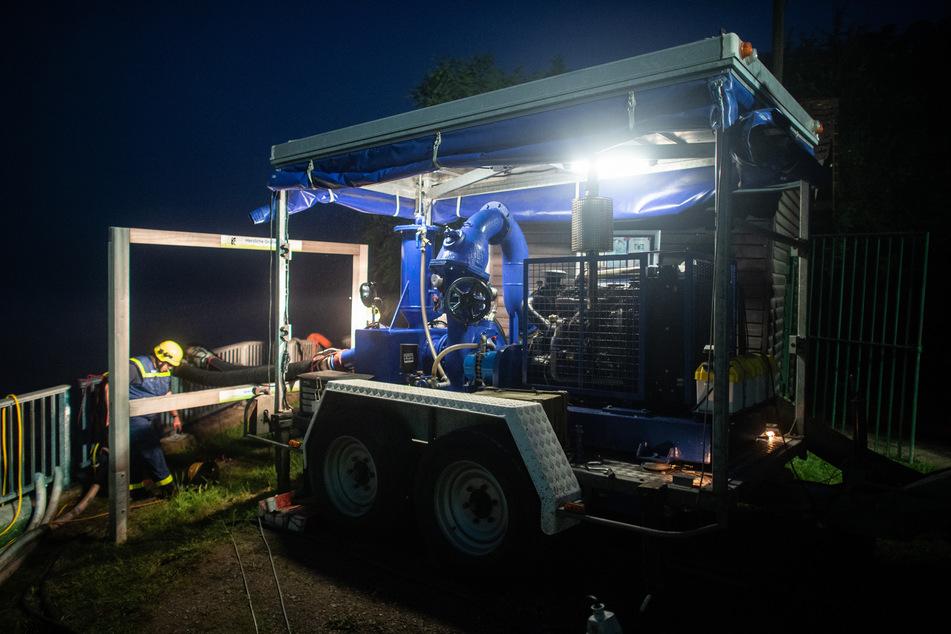 Mitarbeiter des Technischen Hilfswerks (THW) stehen mitten in der Nacht an der Steinbachtalsperre und pumpen Wasser über die Staumauer, um sie zu entlasten. Die Heftige Regenfälle in der Nacht sorgten für Schlammlawinen und Überflutungen.