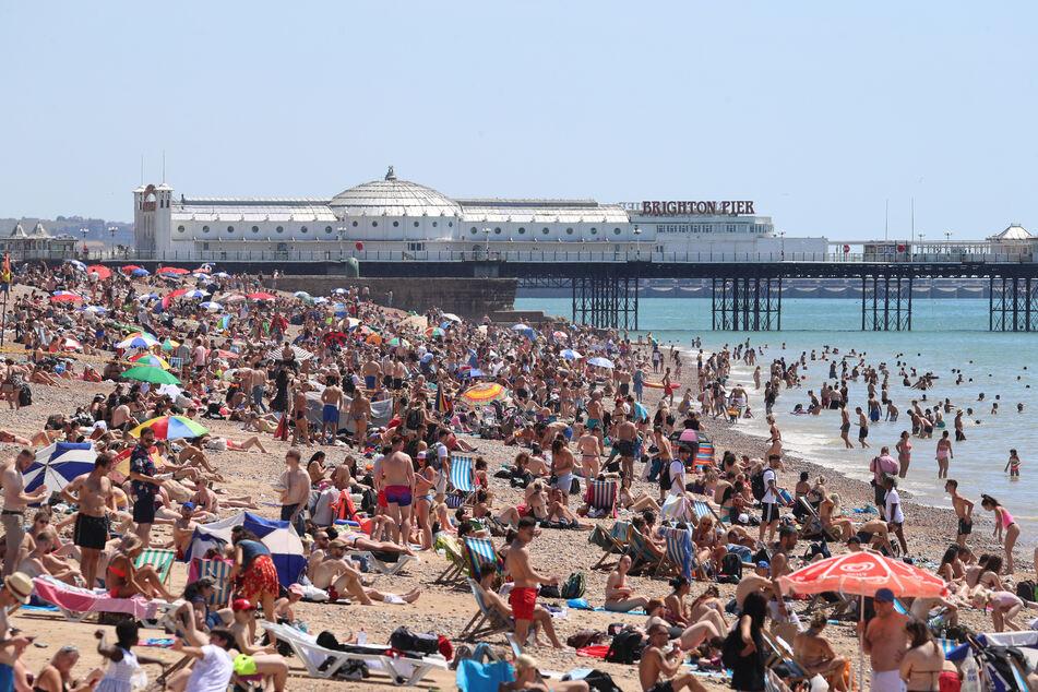 Eine große Menschenmenge verbringt den sonnigen, heißen Tag an einem Kieselstrand in Brighton.