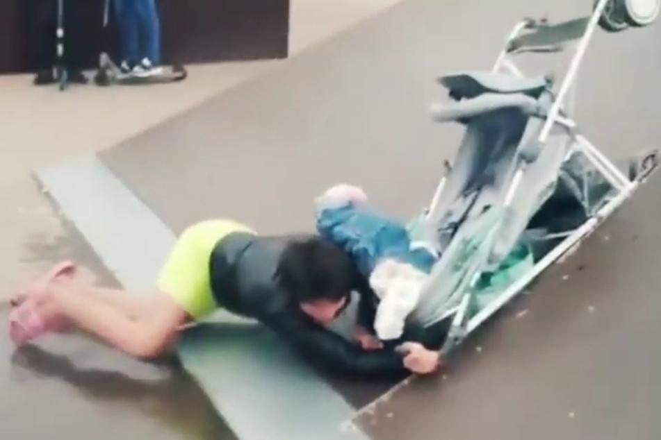 Alle Versuche, über die Rampe zu kommen, gingen schief. Am Ende stürzte die Frau zu Boden und riss den Kinderwagen samt Baby um.