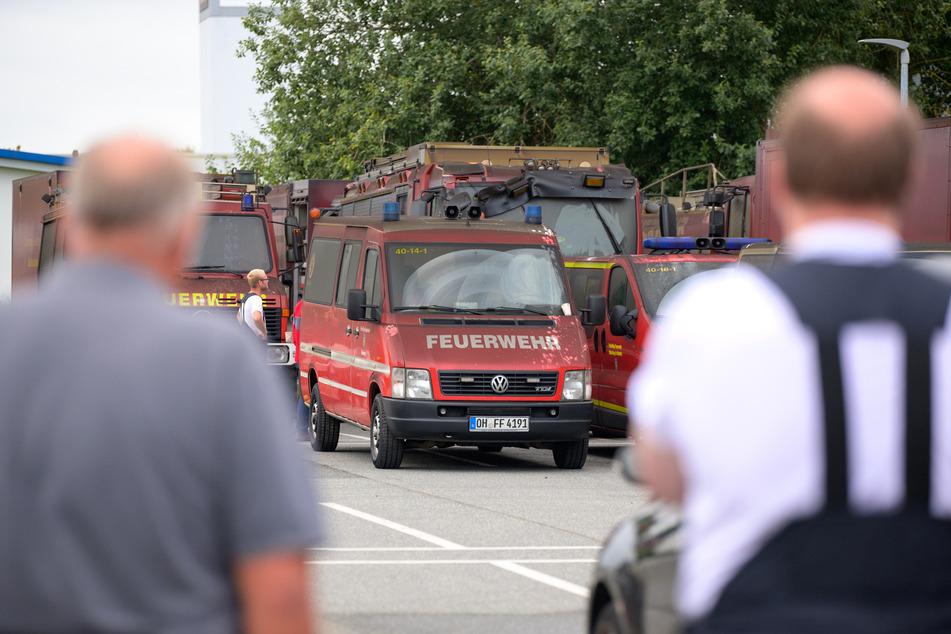Feuerwehrleute schauen auf ihre verrußten und beschädigten Einsatzfahrzeuge.