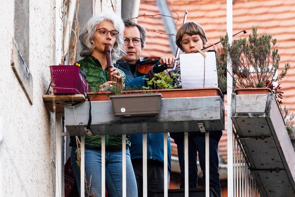 """Heiko Mürbe (m.), Bratscher der Dresdner Philharmonie, spielt mit seiner Frau und seinem Sohn auf dem Balkon die """"Ode an die Freude""""."""
