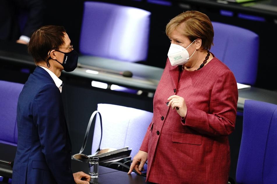 Bundeskanzlerin Angela Merkel (CDU) und der Abgeodnete Karl Lauterbach (SPD) unterhalten sich mit Mund-Nasenbedeckung vor der Sitzung des Bundestages am Donnerstag.