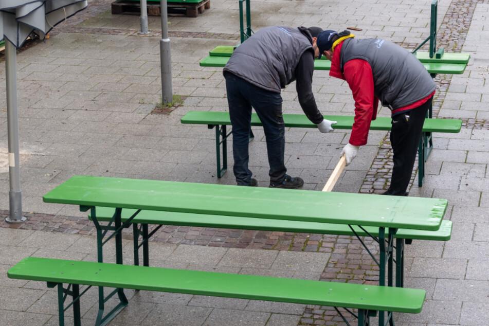 Mitarbeiter des Biergartens am Chinesischen Turm in München bauen Biertische und Bänke mit jeweils 2 Metern Abstand auf.