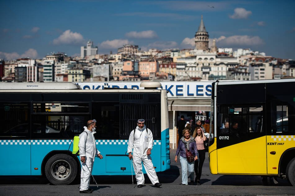 Mitarbeiter der Stadtverwaltung von Istanbul warten darauf, einen Bus zu desinfizieren.
