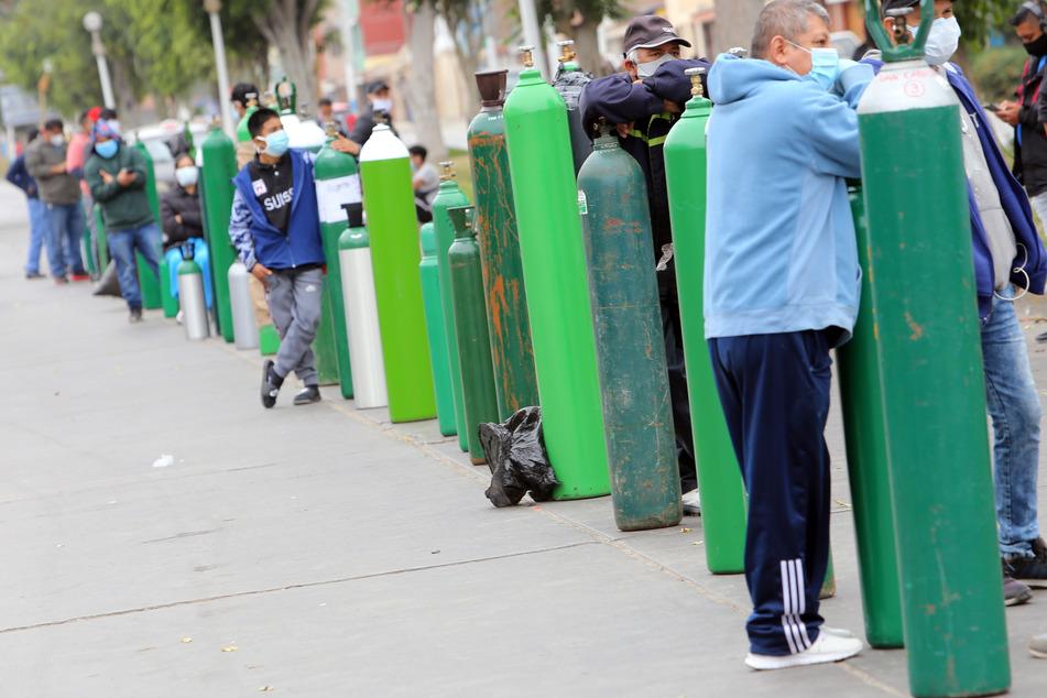 Menschen stehen vor einem Laden in einer Schlange neben ihren Sauerstoffflaschen, damit sie aufgefüllt werden. (Archivbild)