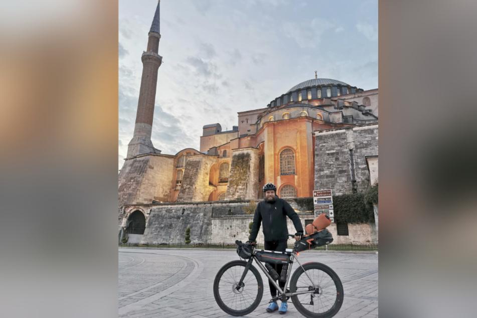 Extremsportler Jonas Deichmann (33) steht mit seinem Fahrrad vor einer Moschee in Istanbul.