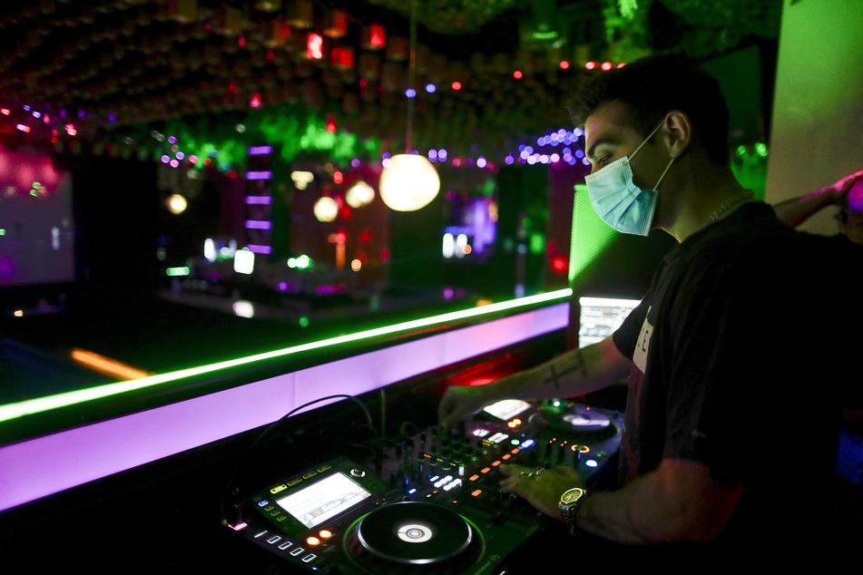 Ein DJ legt am frühen Samstag in einer Diskothek Musik auf.