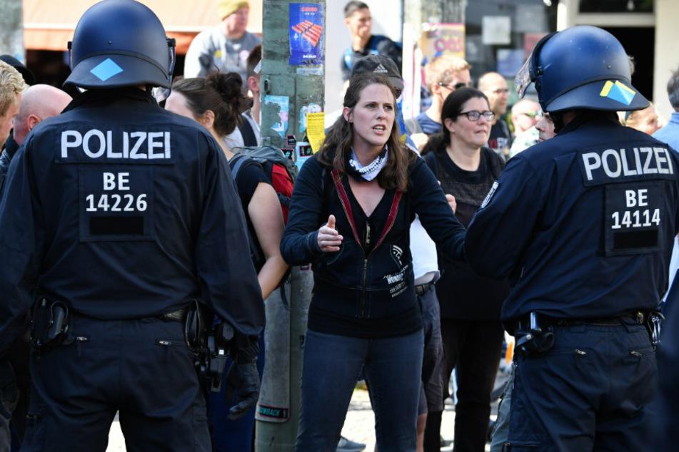 Menschen beobachten vom Straßenrand, wie die Polizei die Kreuzung Torstraße/Friedrichstraße räumt bei einer Demonstration gegen die Corona-Maßnahmen.