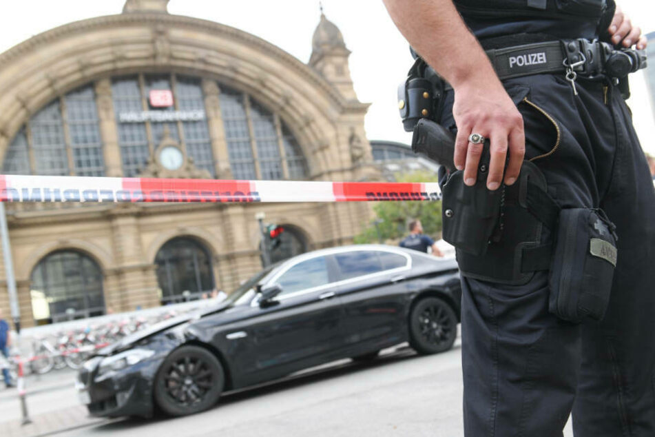 Ein Polizeibeamter steht am Frankfurter Hauptbahnhof vor einem schwarzen BMW, mit dem mehrere Täter dem Raubüberfall geflüchtet waren (Archivbild).