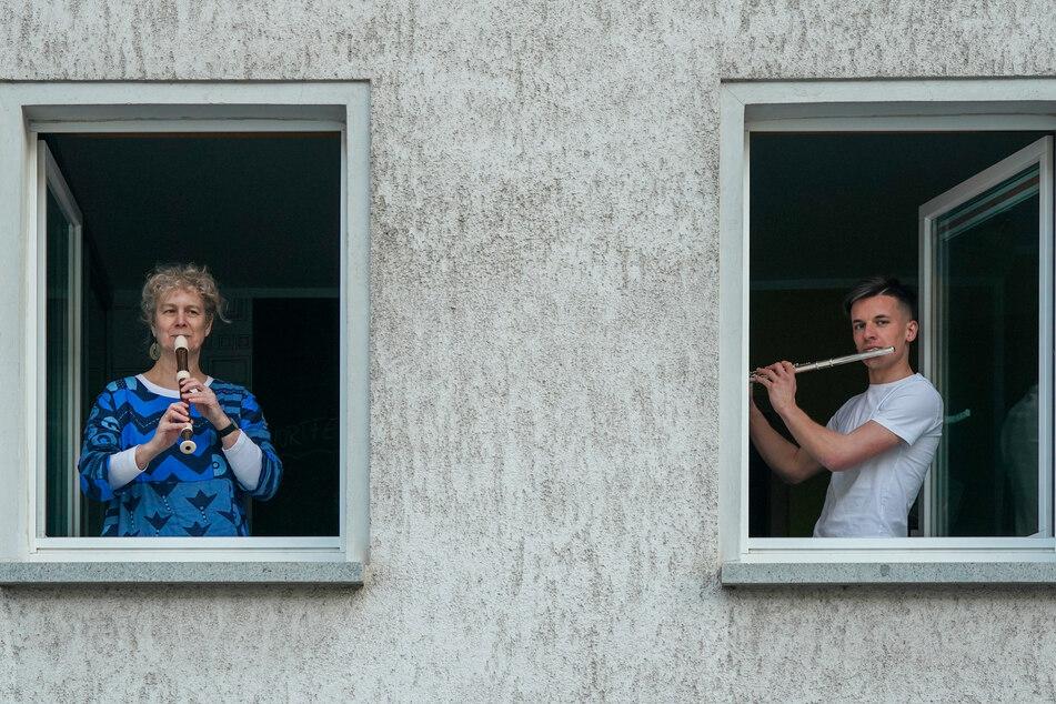 """Ausgangsbeschränkung in Leipzig: Die Hobby-Flötisten Sabine Albani und Martin Lessner spielen """"Ode an die Freude"""" aus einem Fenster."""