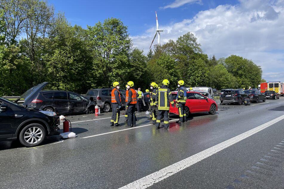 Helfer stehen nach mehreren Auffahrunfälle auf der A2 an den beschädigten Fahrzeugen.