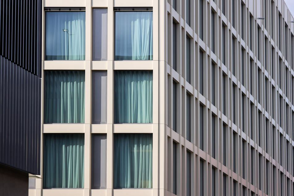 Die Vorhänge hinter sämtlichen Fenstern eines Hotels sind zugezogen.