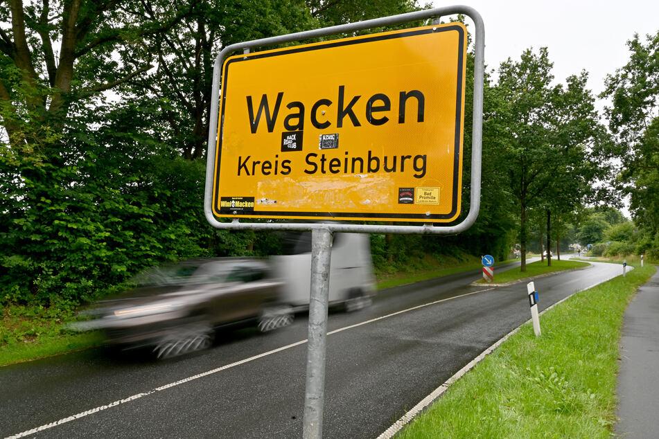 Ein Auto fährt am Ortsschild von Wacken vorbei.