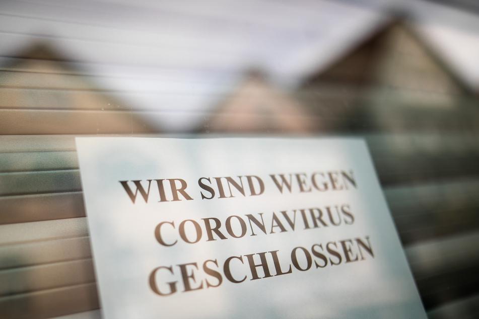 Ein Zettel weist Kunden am Schaufenster eines Geschäfts über die vorübergehende Schließung hin.