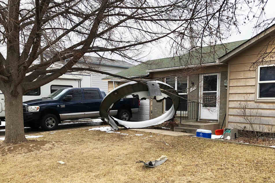 Ein Bauteil eines Flugzeugtriebwerks liegt in einem Vorgarten eines Hauses.