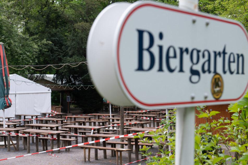 Ein Absperrband umgibt Bänke und Tische in einem geschlossenen Biergarten. Im Freistaat sollen Kneipen, Biergärten und Restaurants ab dem 15. Mai 2020 unter strengen Hygiene-Auflagen wieder öffnen dürfen.