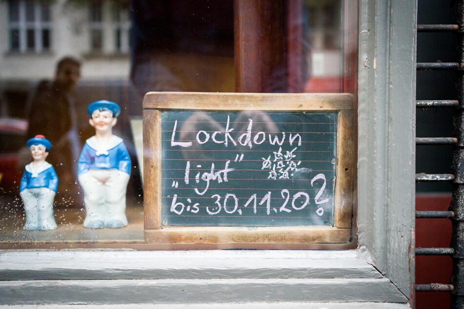 """Eine Tafel mit der Aufschrift """"Lockdown 'light' bis 30.11.20?"""" steht im Schaufenster einer Kneipe im Berliner Stadtteil Schöneberg zu Beginn des einmonatigen Teil-Lockdowns."""