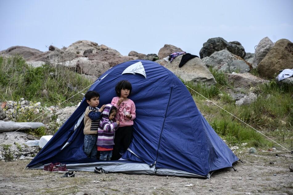 Kinder stehen vor einem Zelt im Dorf Petra auf der nordöstlichen Ägäisinsel Lesbos. Die Corona-Krise gefährdet nach Unicef-Angaben die fragile Grundversorgung der ärmsten Kinder in vielen Entwicklungsländern und Krisengebieten.