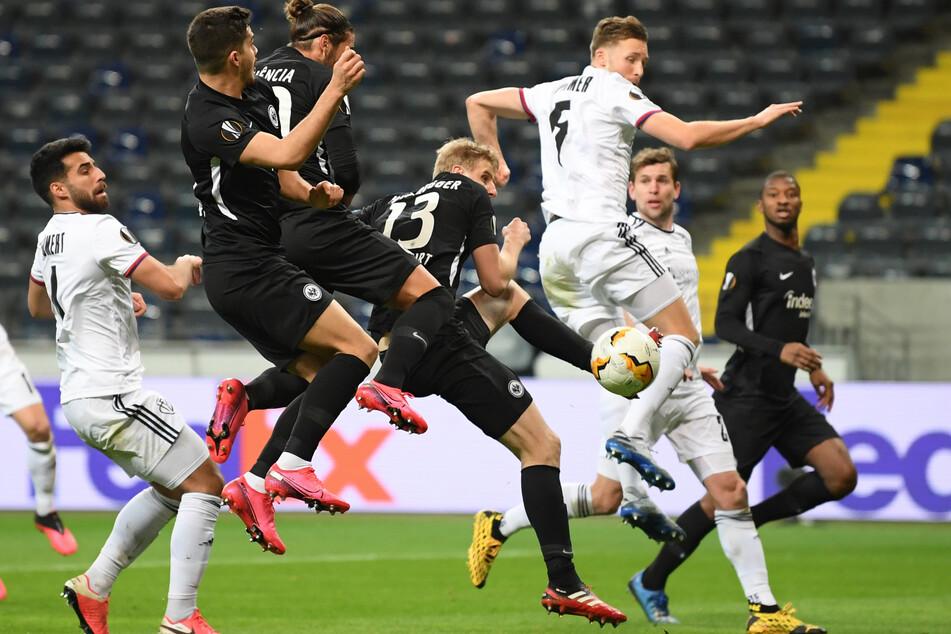 Frankfurts Martin Hinteregger (m., Rückennummer 13) und Basels Silvan Widmer kämpfen im Achtelfinal-Hinspiel der Europa League um den Ball.