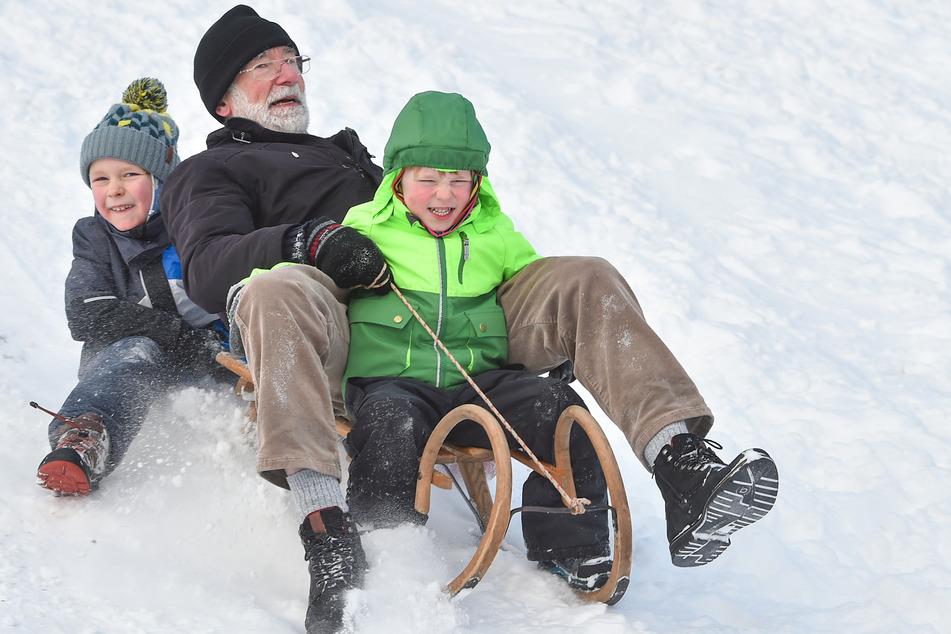 Opa Sighard Jakubski (76) hatte beim Rodeln mit seinen Enkeln Adam (4) und Wanja (7) nahe der Staatskanzlei Freude.