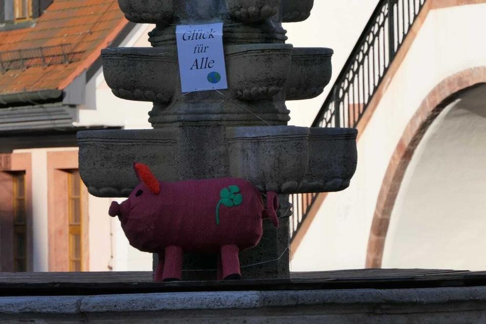 Eine Portion Glück gefällig? Die Bürger von Grimma haben ein süßes Glücksschweinchen auf dem Brunnen abgestellt.