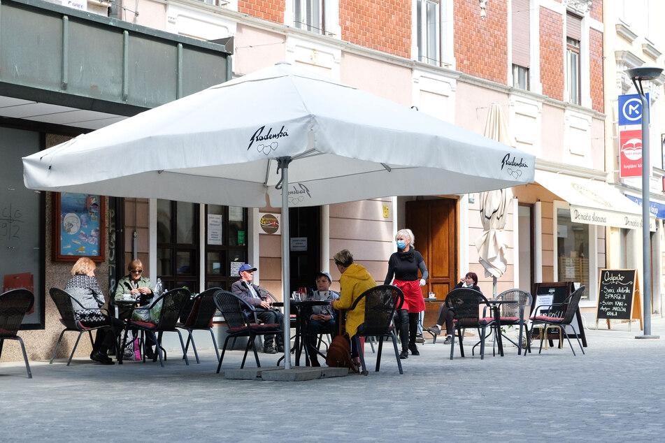 Gäste sitzen im Außenbereich eines Restaurants in der Stadt Celje in Slowenien. Die Neuinfektionen steigen im gesamten Land stark an.