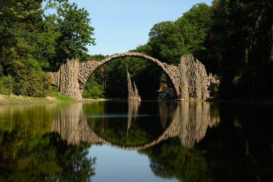 Die Rakotzbrücke bildet einen steinernen Kreis mit dem Wasser im See des Azaleen- und Rhododendren-Parks in Kromlau im Landkreis Görlitz.
